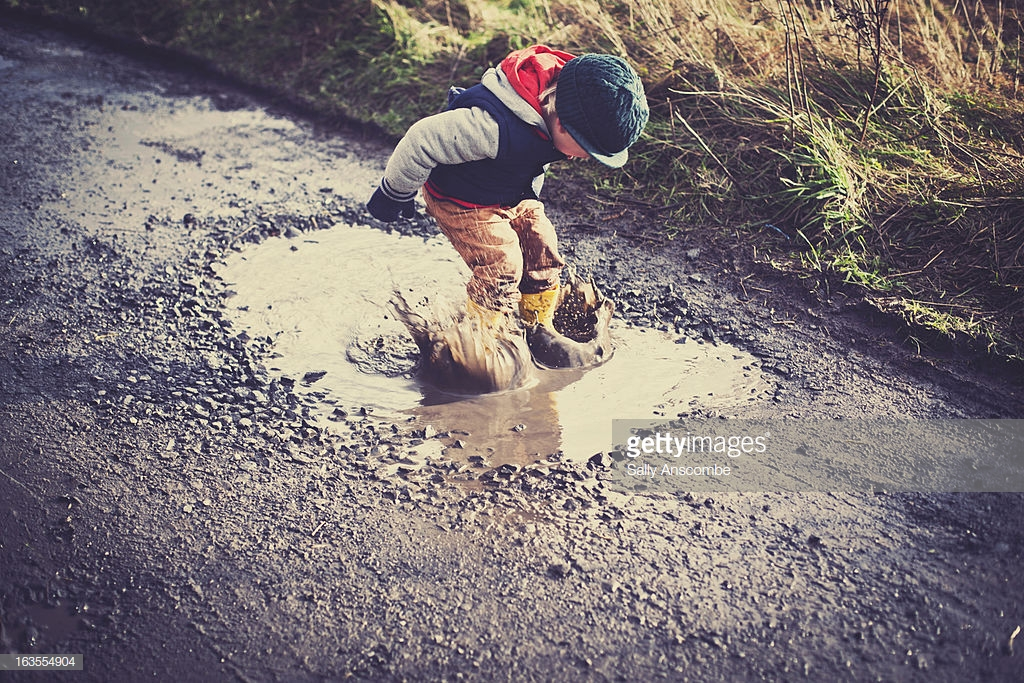 Little boy making a splash jumping in a big muddy puddle.